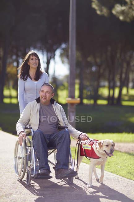 Женщина с собакой в парке и человек в инвалидной коляске — стоковое фото