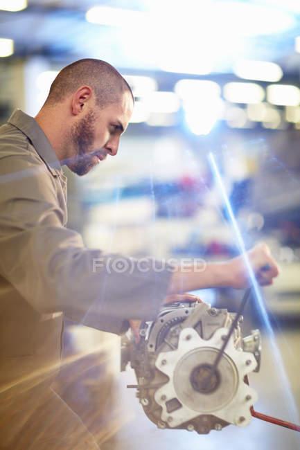 Meccanico di auto che lavora sul cambio in garage di riparazione — Foto stock