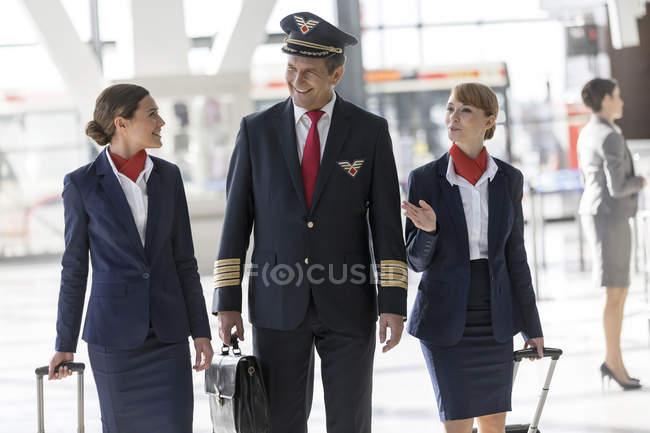 Pilot And Flight Attendants Walking At The Airport U2014 Stock Photo