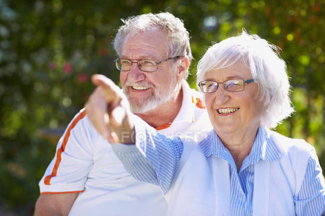 Senior couple pointing at something  in park — Stock Photo