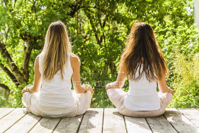 Две женщины практикуют йогу на открытом воздухе — стоковое фото