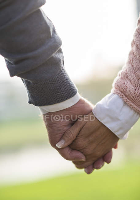 Daughter holding hand of senior man — Stock Photo