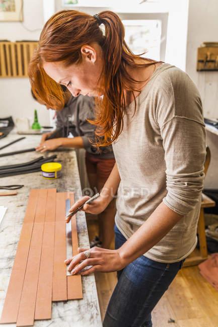 Женщина режет резинку из эластичной ткани в шортах — стоковое фото