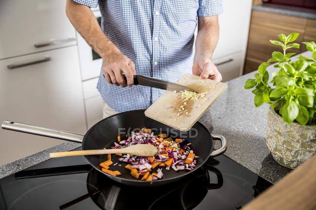 Man  putting cutted garlic into frying pan — Stock Photo