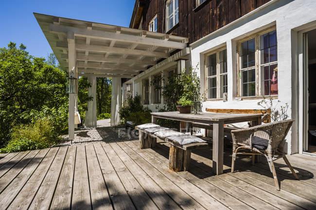 Дерев'яною терасою зі столиком і лавки у sunlight — стокове фото