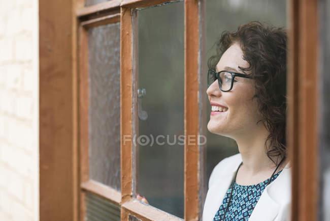 Lächelnde junge Geschäftsfrau aus Fenster — Stockfoto