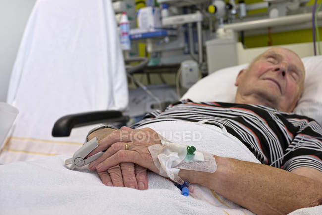 Senior man with cannulae and band-aid lying on bed — Stock Photo