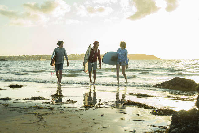 Teenagers with surfboards walking on beach at sunset — Stock Photo