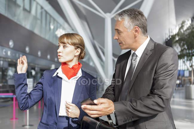Auxiliar de vuelo, asistencia a pasajeros en el aeropuerto - foto de stock