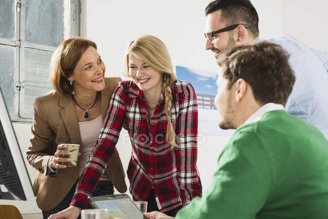 Cuatro empresarios felices en la oficina moderna - foto de stock