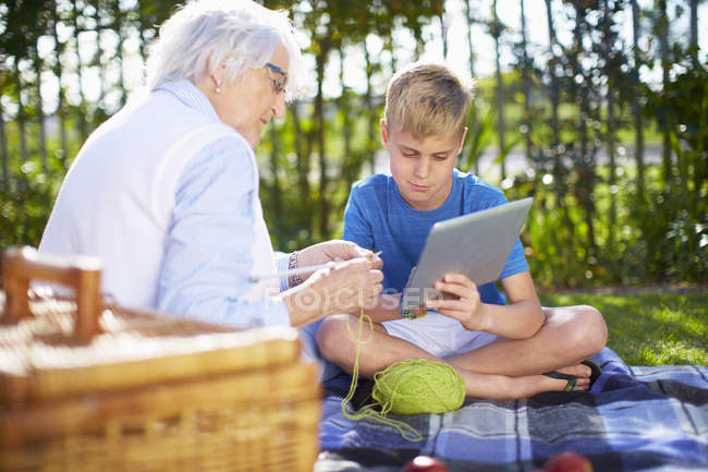 Grandson with digital tablet and grandmother on picnic blanket — Stock Photo