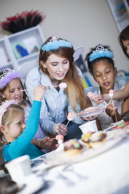 Girls and teenage girl on a birthday party wearing diadems — Stock Photo