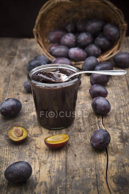 Preservando o pote de geleia de ameixa e ameixas na mesa de madeira — Fotografia de Stock
