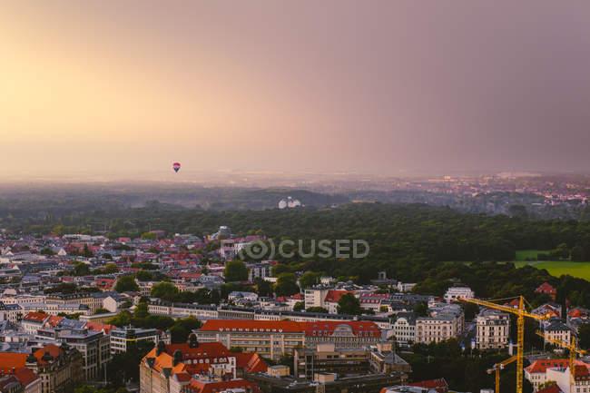 Globo de aire caliente flotando sobre la ciudad en el crepúsculo vespertino, Leipzig, Alemania - foto de stock