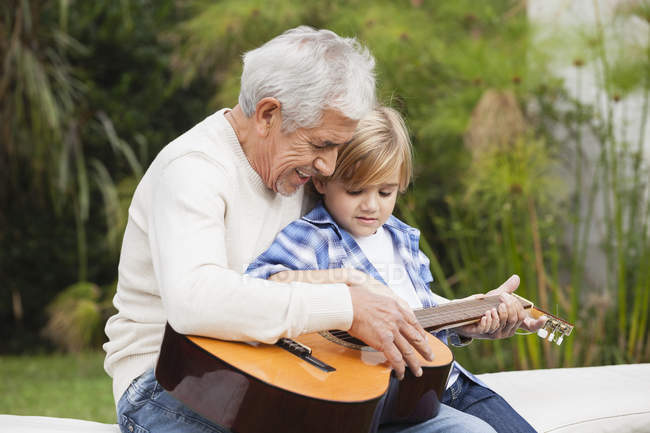 Grandfather and grandson with guitar on bench outdoors — Stock Photo