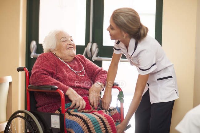 Nurse caring for senior woman in wheelchair — Stock Photo