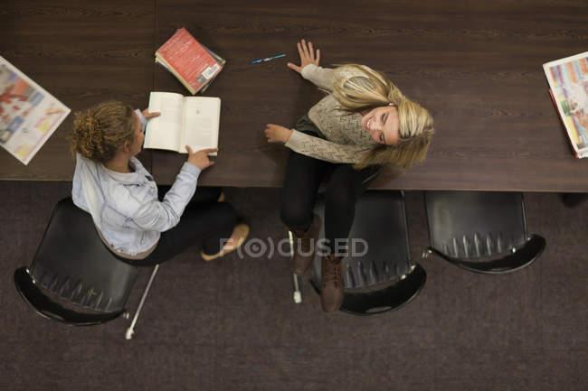 Две студентки за столом в библиотеке — стоковое фото