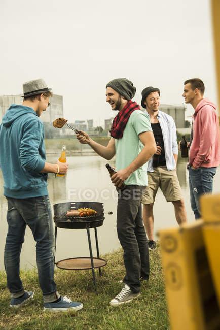 Group of friends drinking beer and having a barbecue — Stock Photo