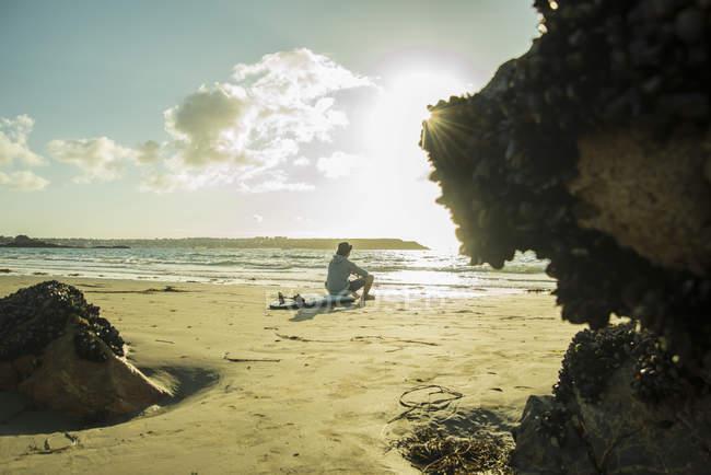Adolescent assis sur la plage en regardant le coucher du soleil — Photo de stock