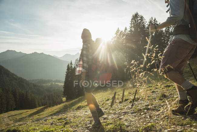 Austria, Tyrol, Tannheimer Tal, young couple hiking in sunlight on alpine meadow — Stock Photo