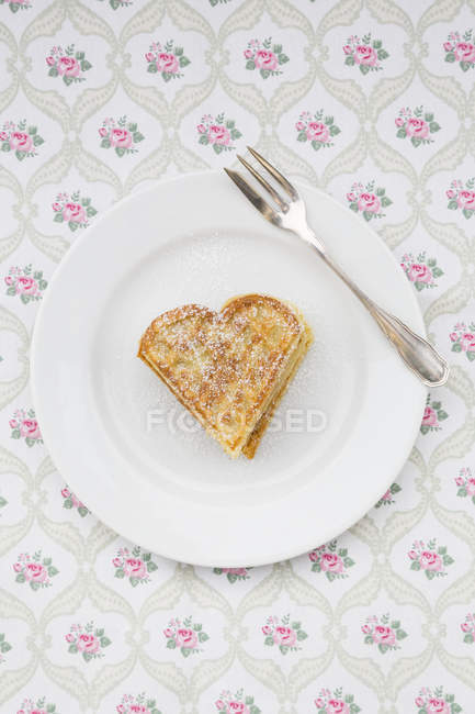 Piatto del cuore a forma di cialde cosparso di zucchero sul panno modellato a velo — Foto stock
