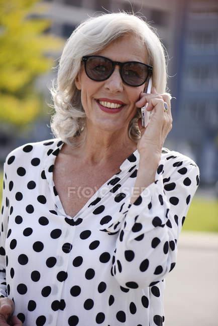 Портрет улыбаясь старшие женщины носить солнцезащитные очки, Телефонировать с смартфон — стоковое фото