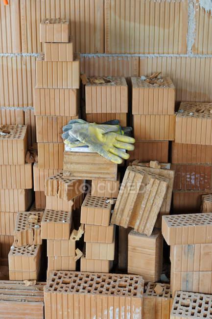 Arbeitshandschuhe auf einem Ziegelstapel auf dem Gelände eines Wohnhauses — Stockfoto