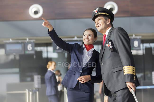 Sonriendo el piloto y la azafata en el aeropuerto - foto de stock