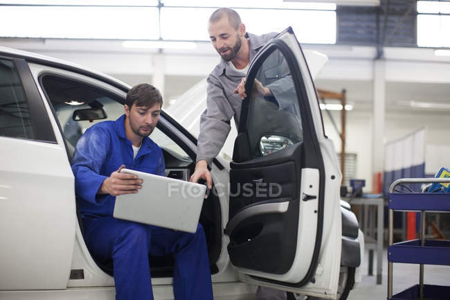 Two car mechanics with laptop in repair garage — Stock Photo
