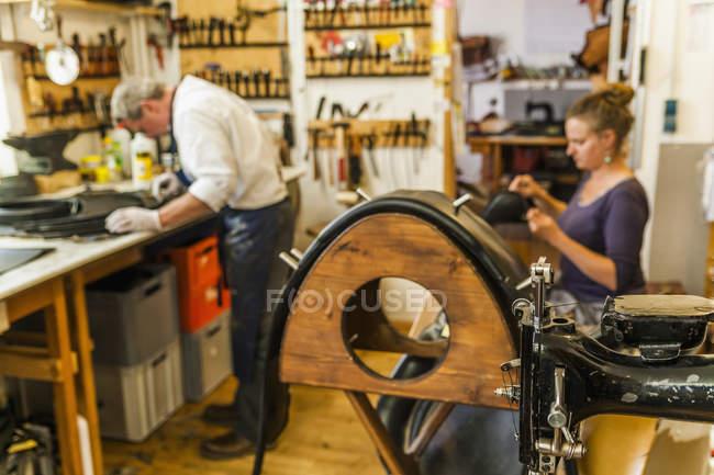 Vautling ремень и кожа швейная машина в шорные изделия с работниками на фоне — стоковое фото