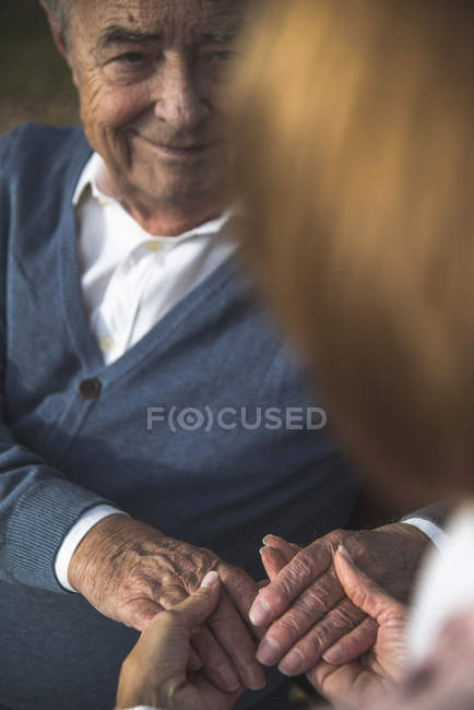 Daughter holding hands of senior man — Stock Photo