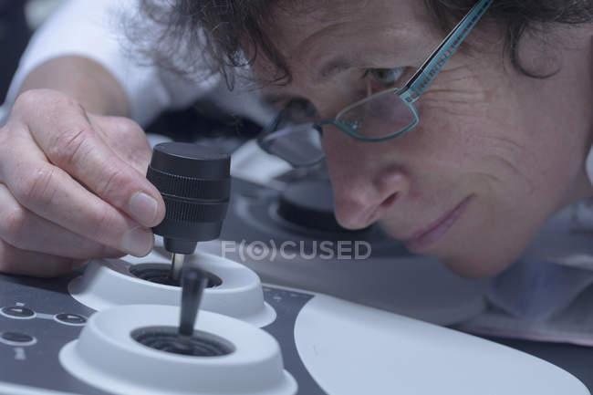 Especialista en soporte técnico femenino que controla una herramienta técnica con un palo - foto de stock