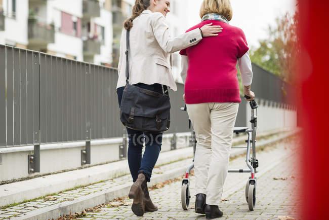 Adulte petite-fille aider sa grand-mère à marcher avec marcheur à roues, vue de dos — Photo de stock