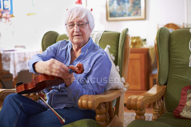 Senior woman at home tuning violin — Stock Photo