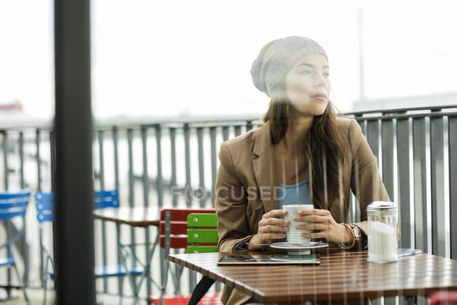 Mujer sentada en el café de la acera - foto de stock