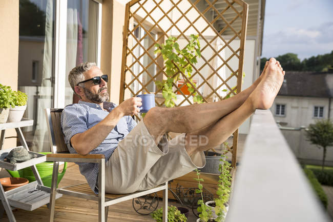 Man wearing sunglasses relaxing on his balcony with a cup of coffee — Stock Photo