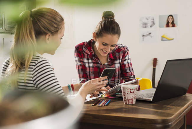 Two female friends with smartphone, laptop and digital tablet at home — Stock Photo