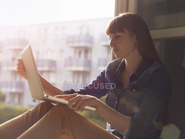 Woman at open window using laptop — Stock Photo