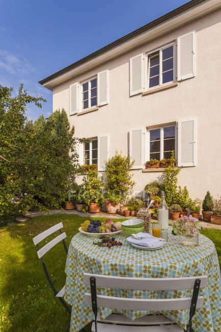 Colazione sana sul tavolo da giardino contro casa — Foto stock