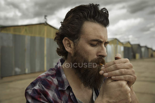 Man with full beard lighting cigarette — Stock Photo