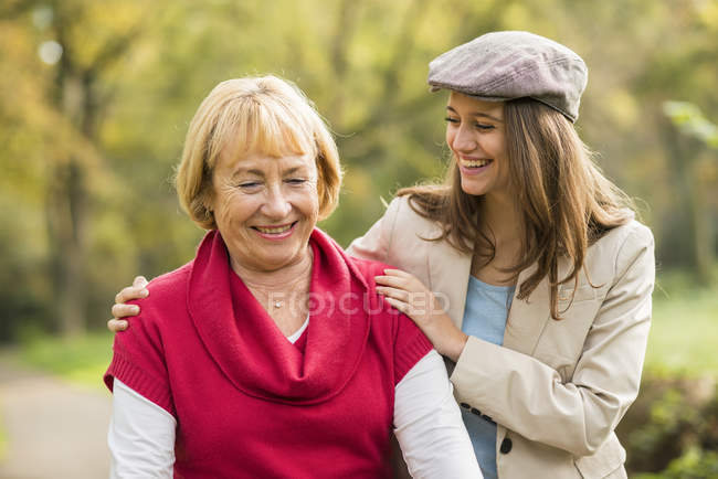 Smiling senior woman and granddaughter walking together in a park — Stock Photo