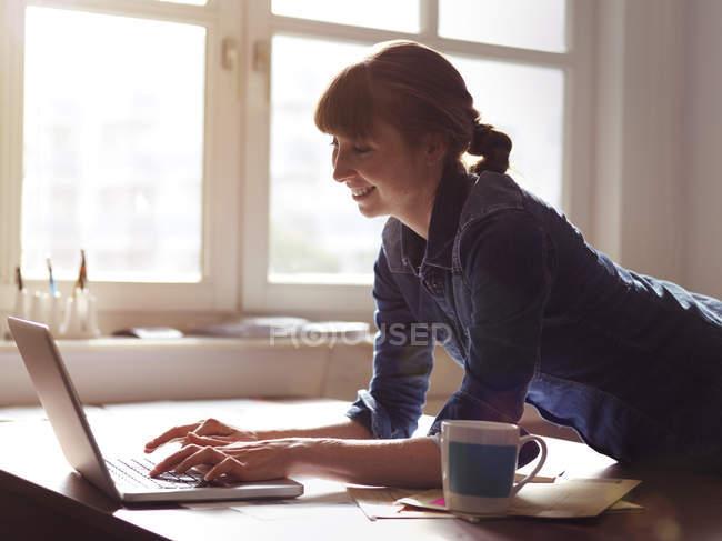 Donna sorridente alla scrivania utilizzando il computer portatile — Foto stock