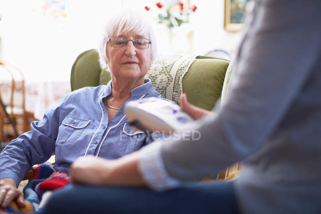Medic caring for senior woman at home — Stock Photo