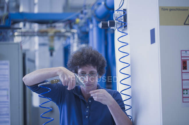 Female technical support specialist spraying with a tool in a technical lab — Stock Photo