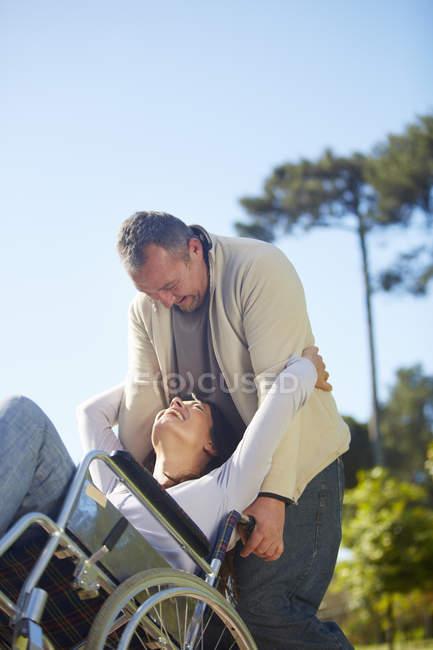 Felice uomo abbracciare donna in sedia a rotelle nel parco — Foto stock