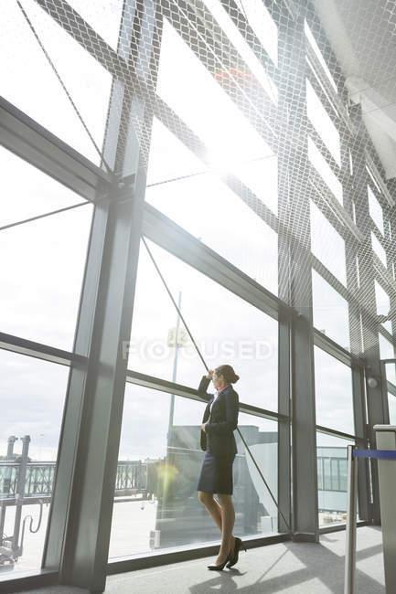 Auxiliar de vuelo en el aeropuerto fuera de ventana - foto de stock