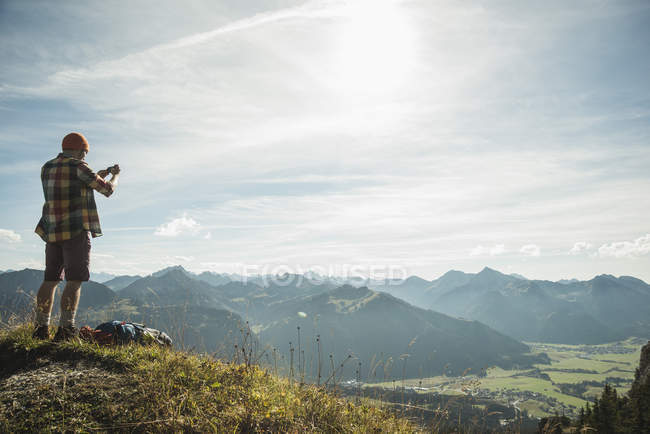 Austria, Tyrol, Tannheimer Tal, young man taking picture in mountainscape — Stock Photo