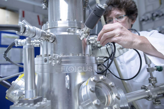 Female technical support specialist working at spectrometer in a technical lab — Stock Photo