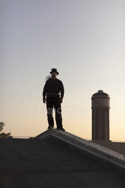 Spazzacamino in piedi sul tetto al crepuscolo — Foto stock