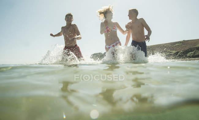 Drei lachende Teenager rennen ins Meer — Stockfoto
